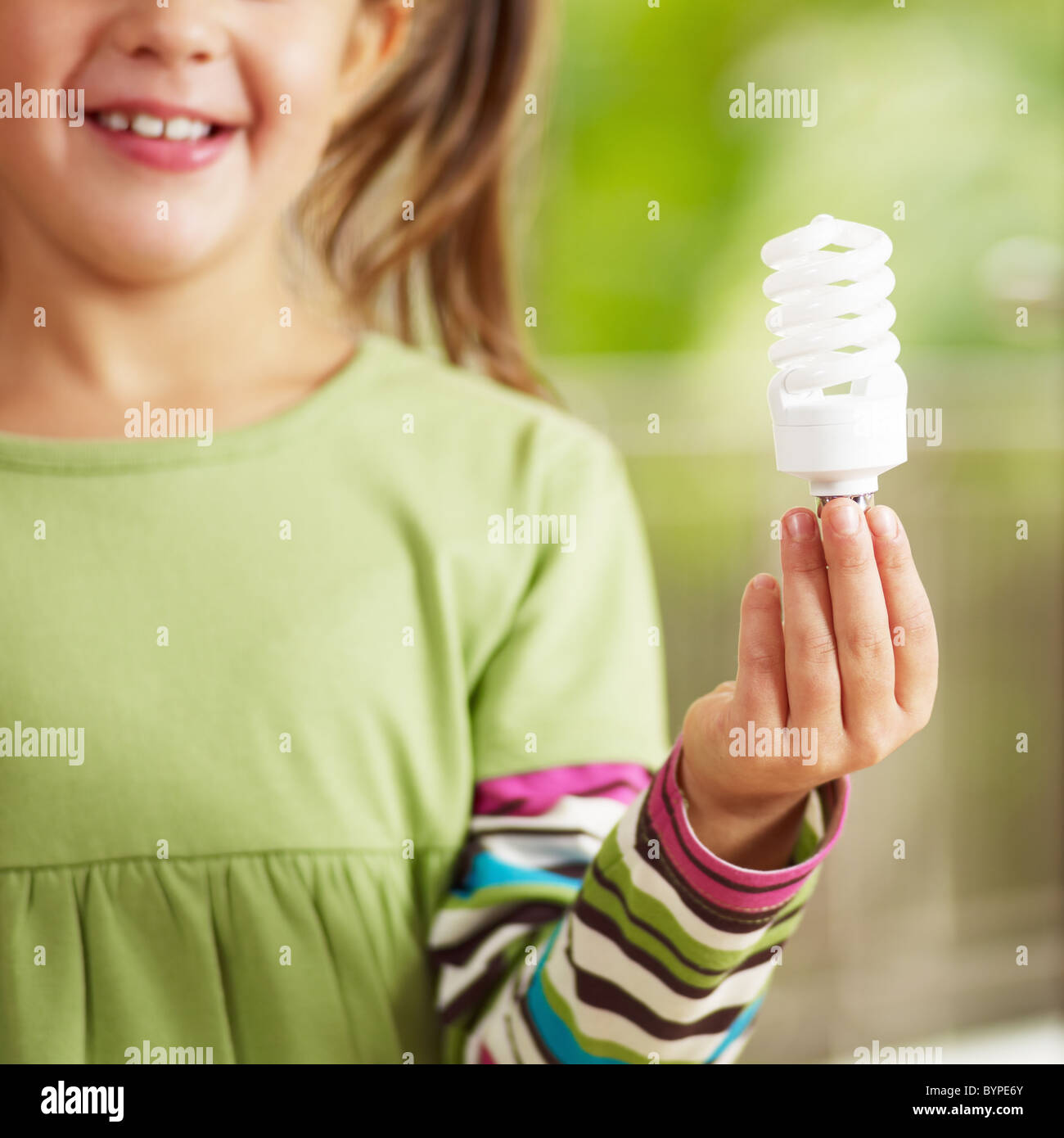 Girl holding light bulb and smiling. Selective focus - Stock Image