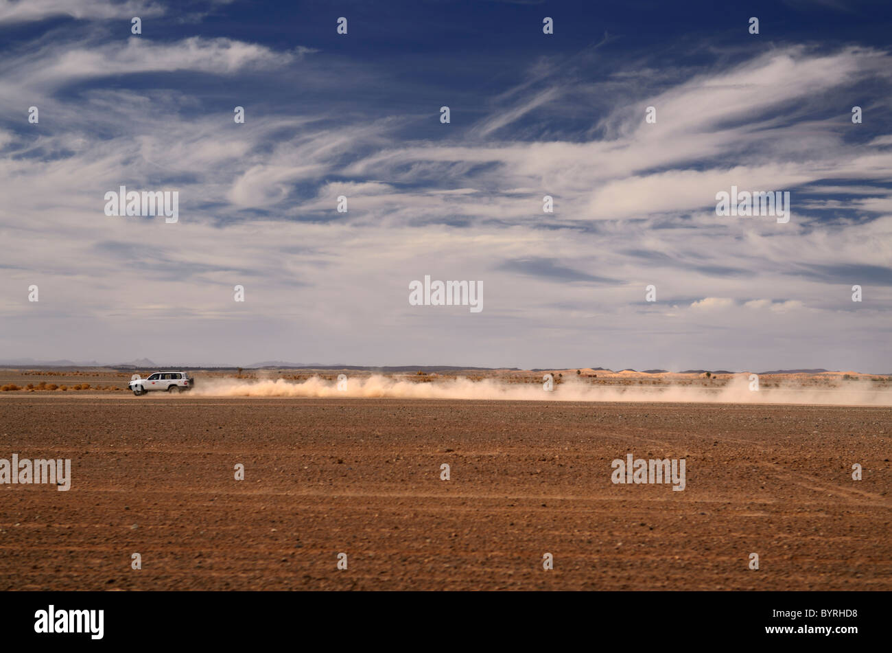 Long dust trail of 4x4 off road car speeding from Erfoud to the Erg Chebbi desert Morocco North Africa - Stock Image