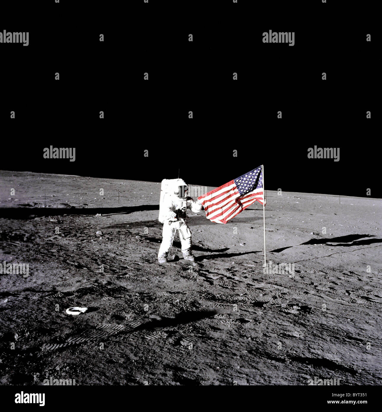 Apollo 12 astronaut Charles 'Pete' Conrad stands beside the United States flag on the moon. - Stock Image