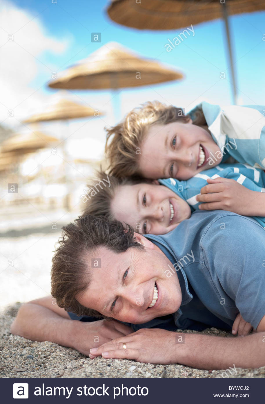 Dad with two sons in a pile on beach - Stock Image