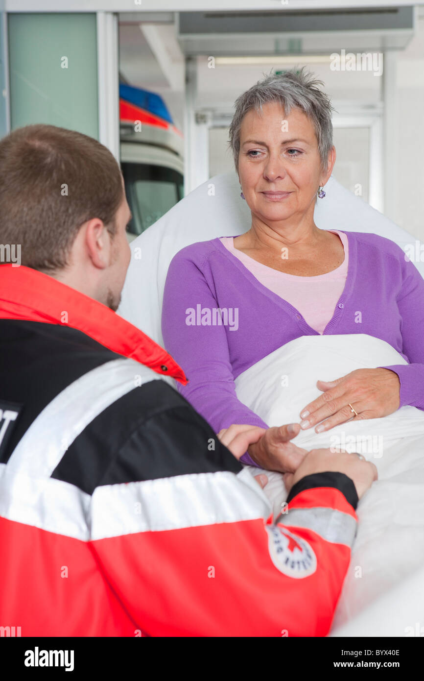 Paramedic caring about woman - Stock Image