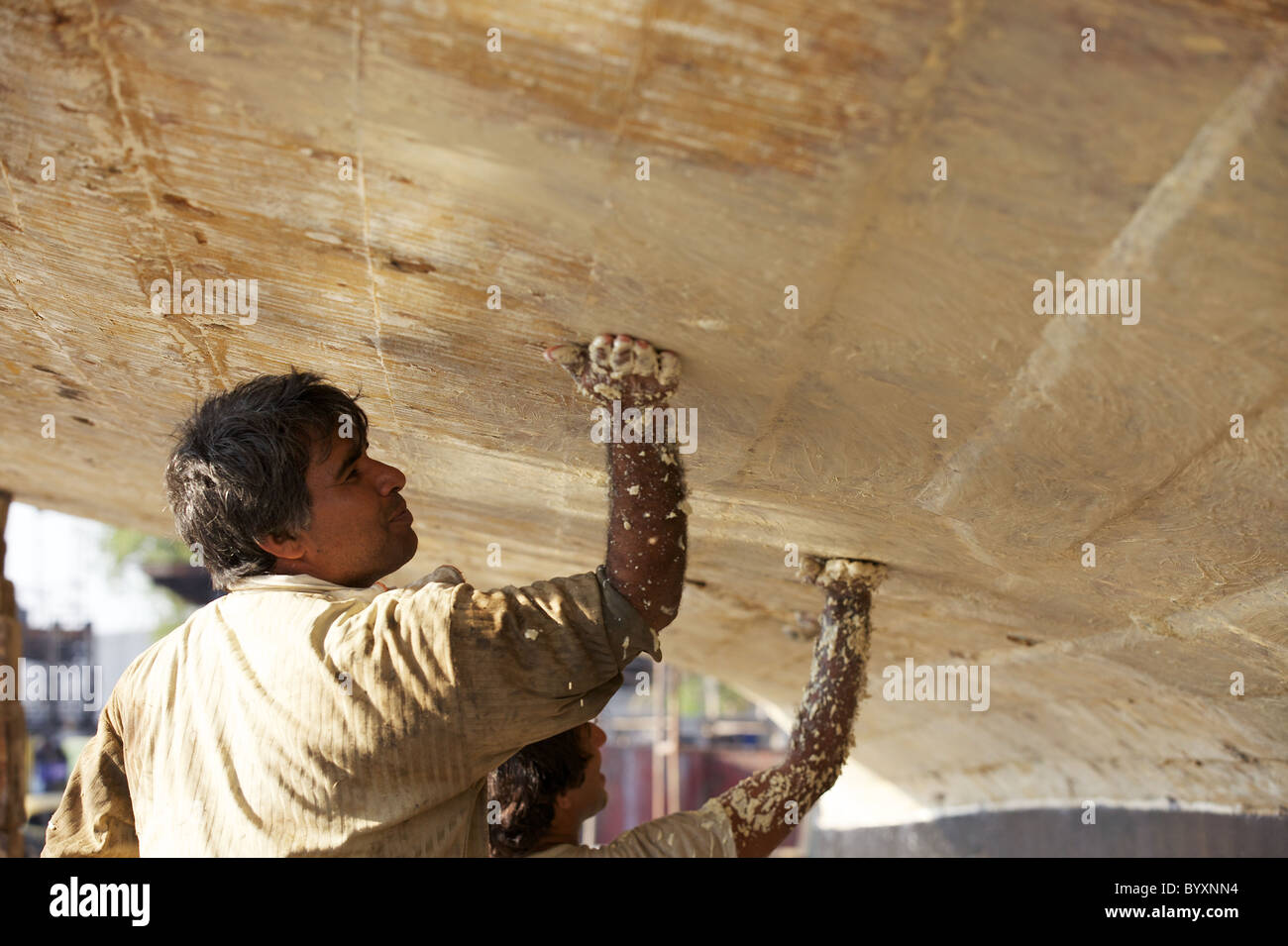 Two workers apply a sealer to the underside of a dhow in the Jaddaf boatyard, Dubai, UAE - Stock Image