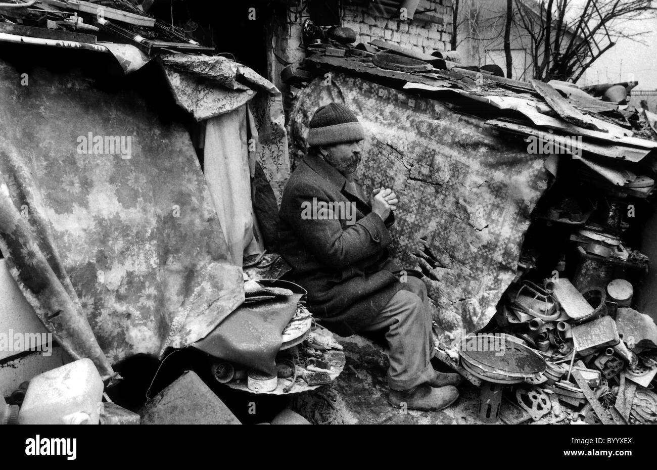 Man sitting in remains of his home destroyed in  Bosnian herzegovina war - Stock Image