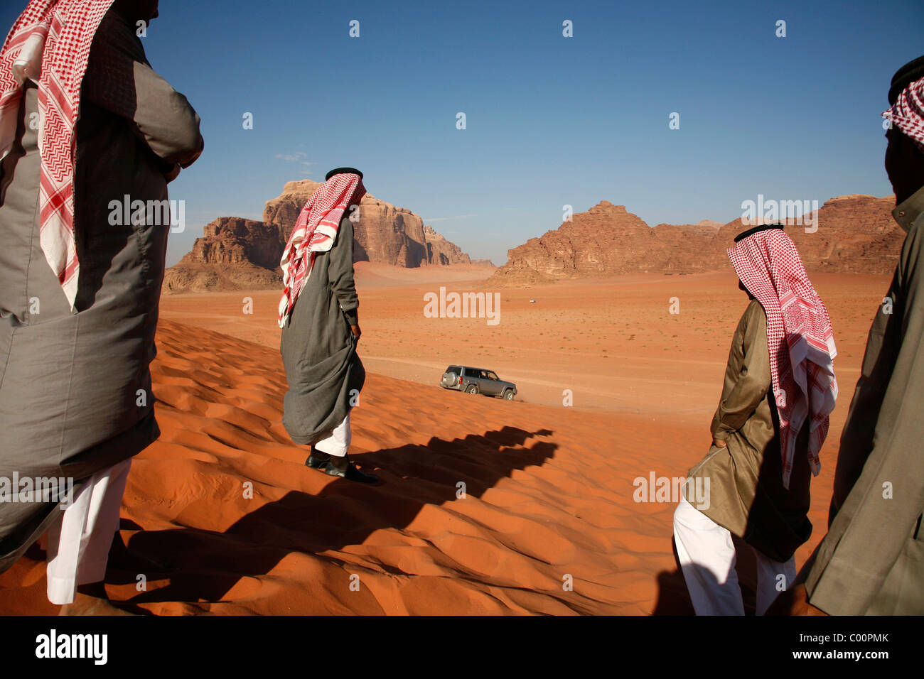 Arab people and a jeep on a red sand dune in Wadi Rum, Jordan. - Stock Image