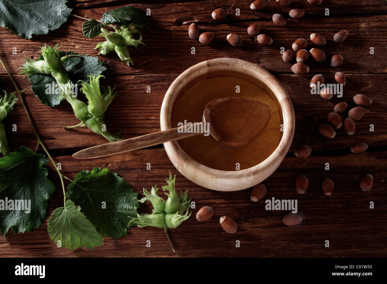 A bowl of hazelnut oil and some ripe and unripe hazelnuts (Corylus avellana) on rustic wooden boards - Stock Image