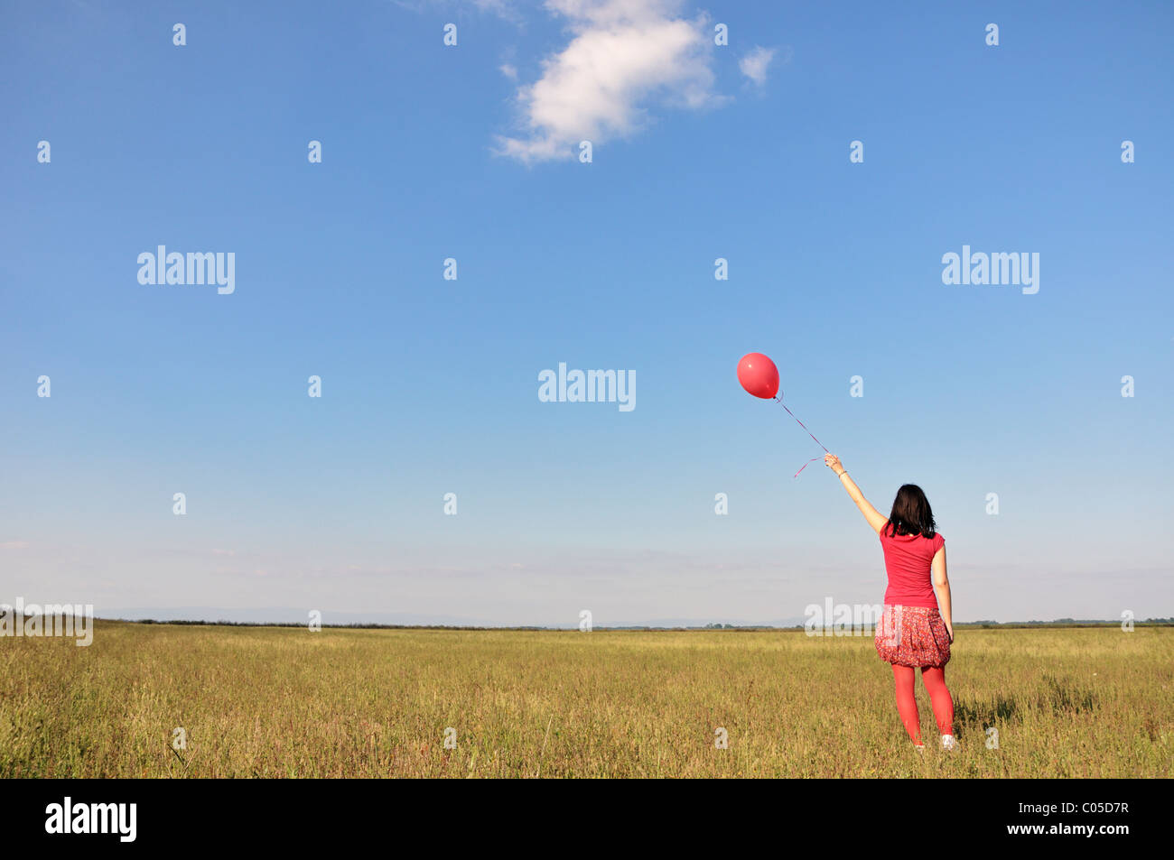 Happy young woman holding red balloon - Stock Image