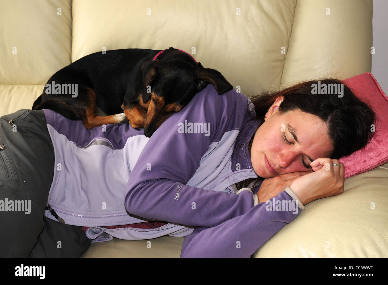 a-dog-curled-up-asleep-on-a-sleeping-woman-C05WWT.jpg