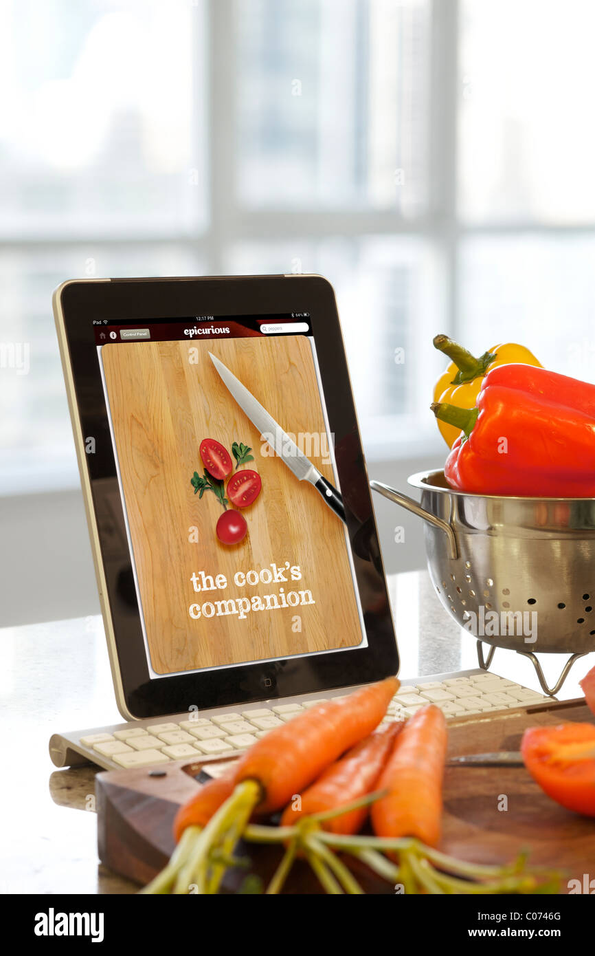 iPad Epicurious cooking application screen being used in the kitchen - Stock Image