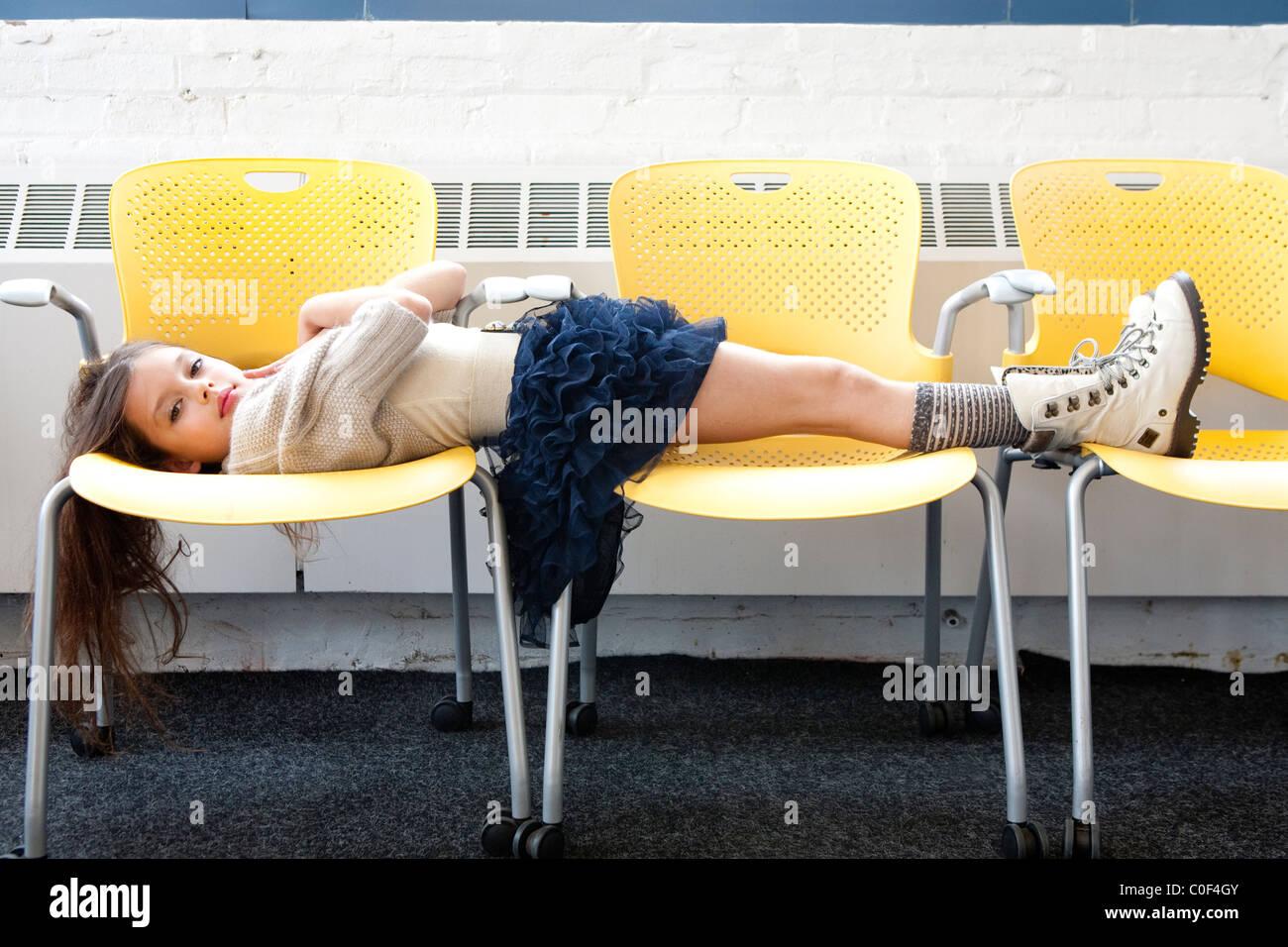 Girl laying across yellow chairs - Stock Image