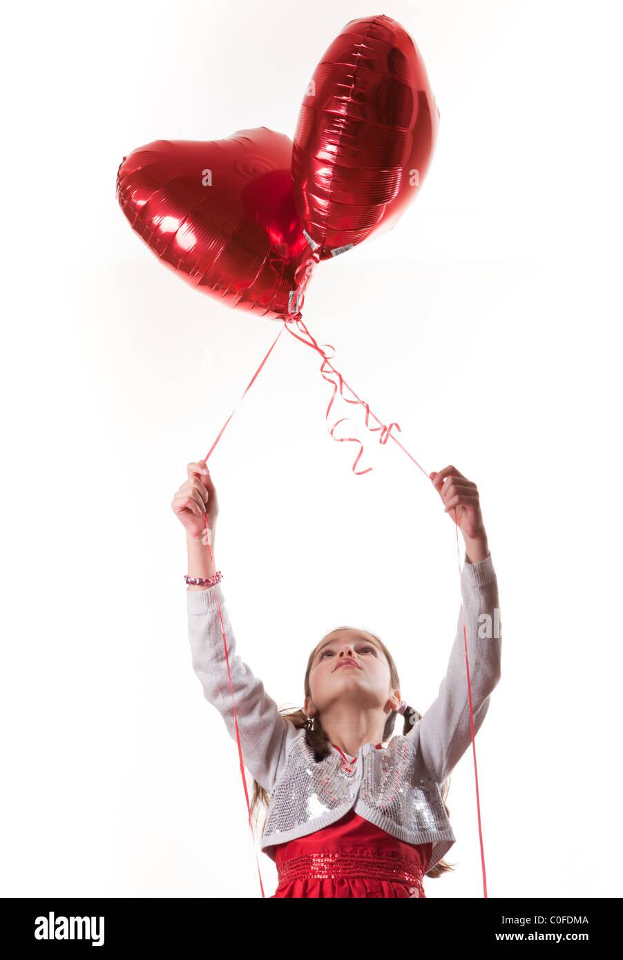 happy girl holding heart shaped balloons - Stock Image