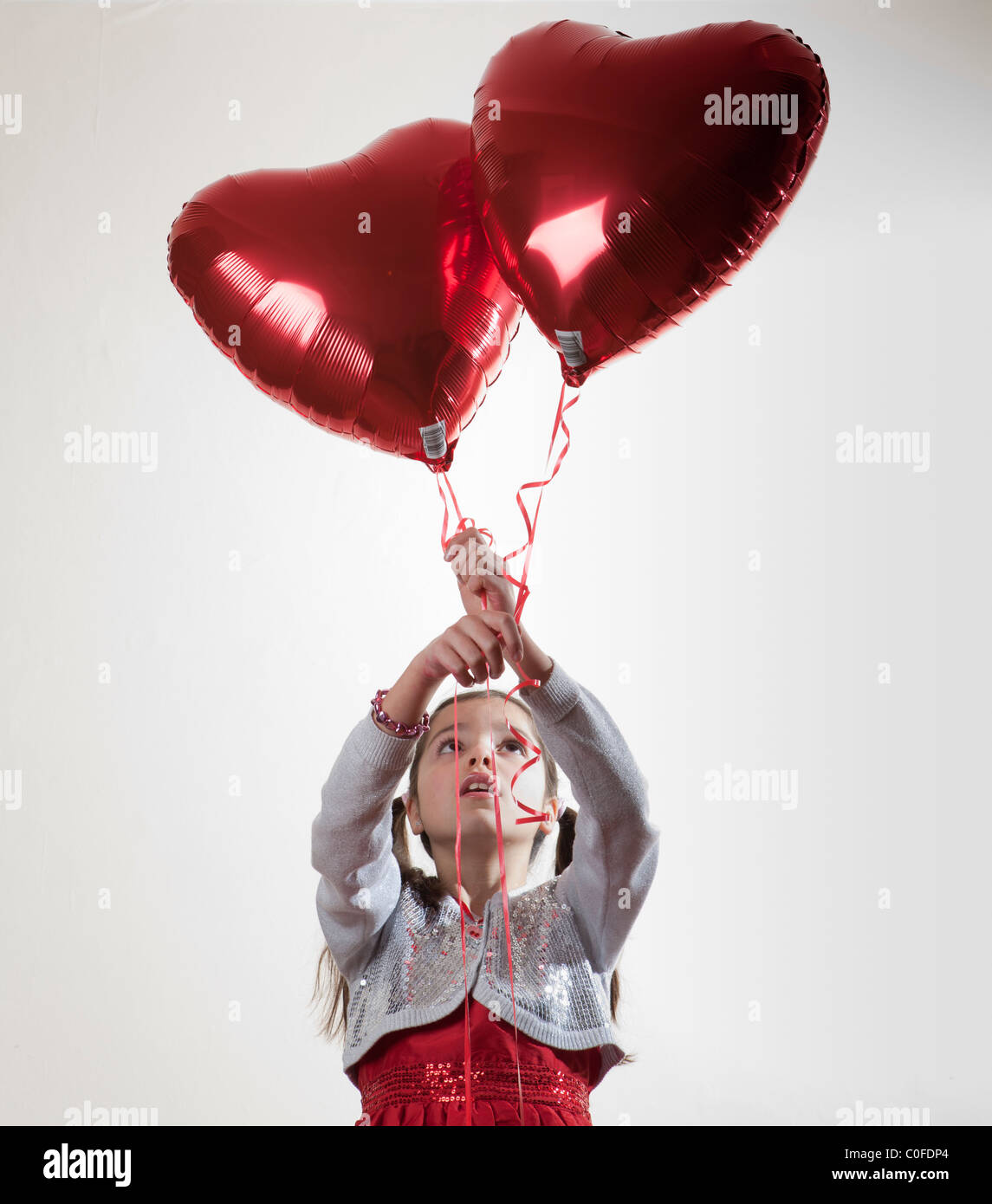 happy girl holding a heart shaped balloon - Stock Image