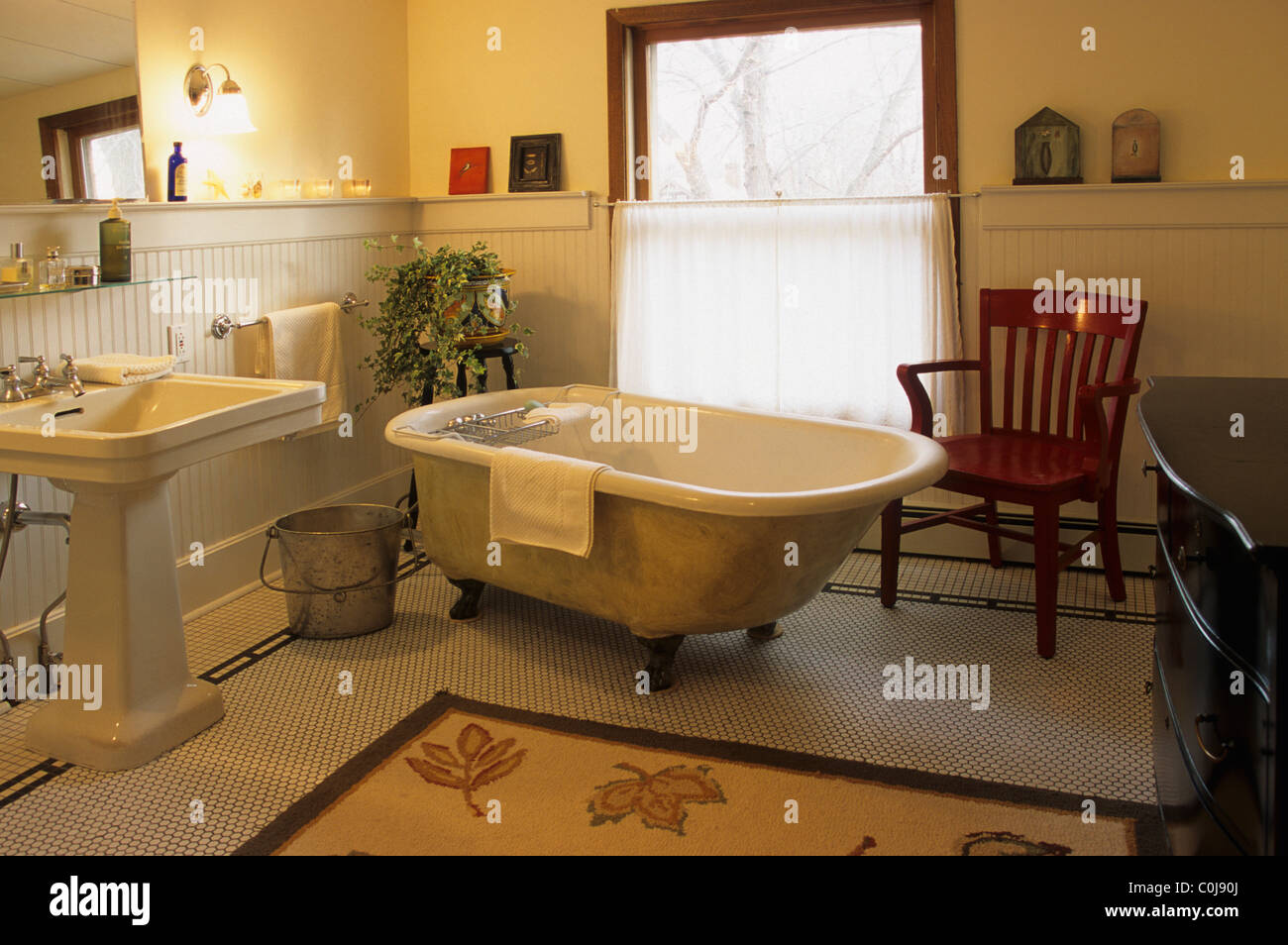 OLD FASHIONED CAST IRON CLAWFOOT BATHTUB AND PEDESTAL SINK IN BATHROOM OF  1920u0027S BUNGALOW STYLE HOME IN MINNESOTA