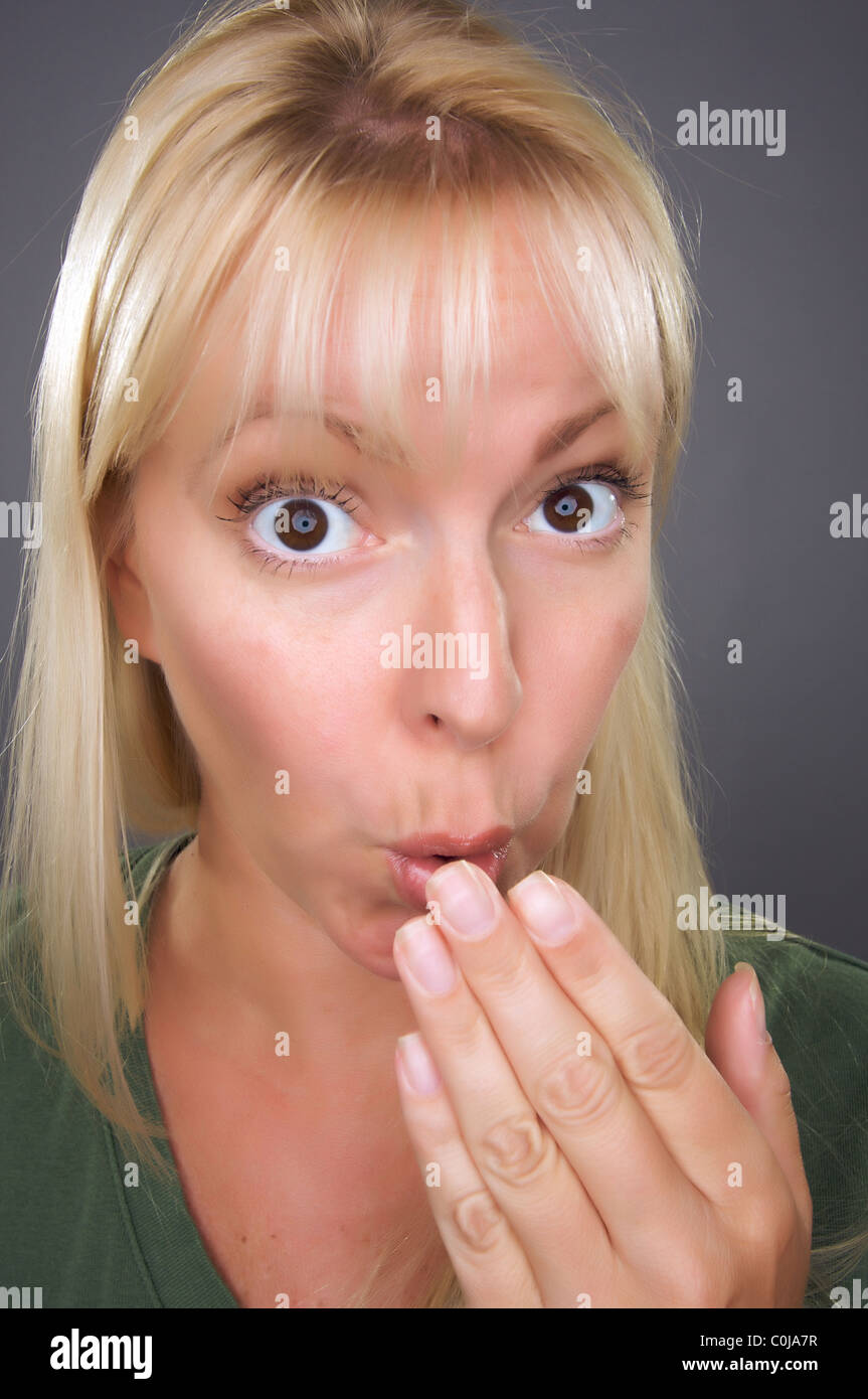 Shocked Blond Woman with Hand in Front of Mouth Against a Grey Background - Stock Image