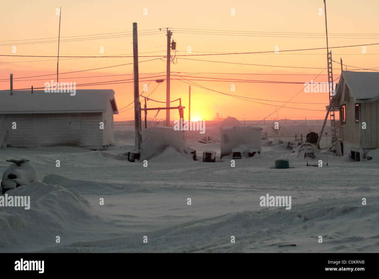 First sunrise in 84 days in Barrow, AK in the Arctic Circle looking past some civilian homes with the airfield in Stock Photo