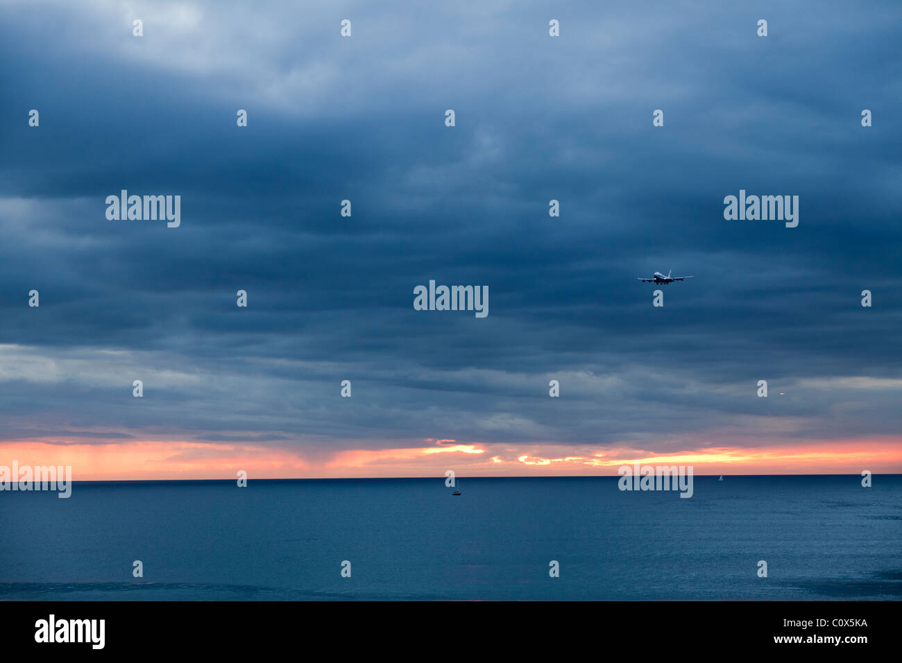 Aircraft passenger jet landing over ocean against cloudy dramatic sky. Dockweiler Beach in Los Angeles, California. - Stock Image
