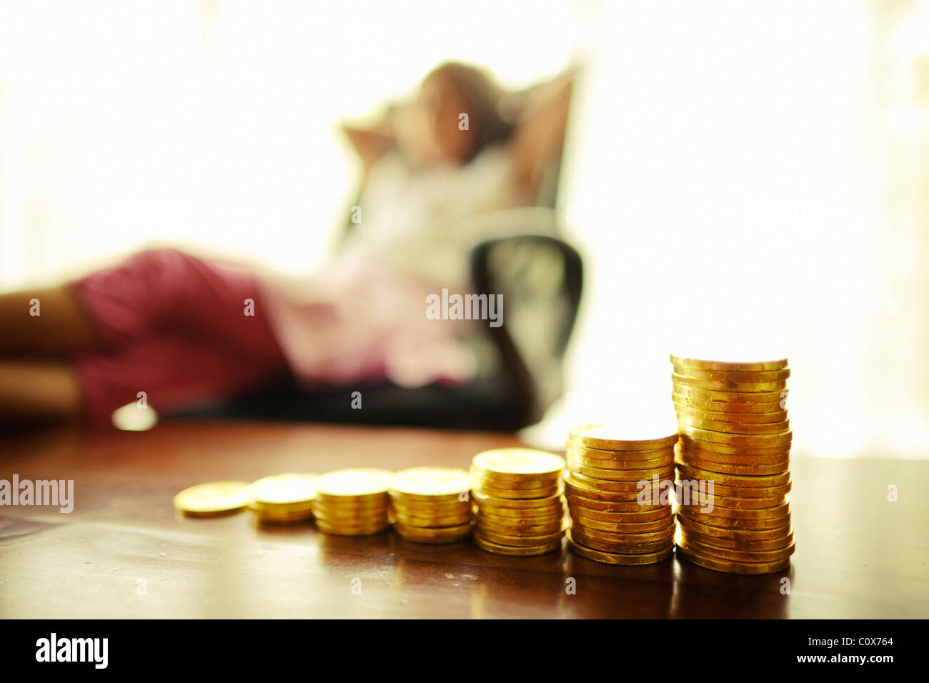 Investing in gold. Girl with stacked chocolate gold coins. - Stock Image