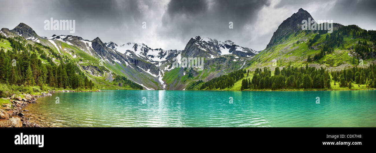 Mountain landscape with turquoise lake and cloudy sky - Stock Image