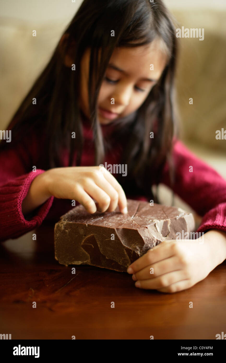 Girl with large brick of chocolate - Stock Image