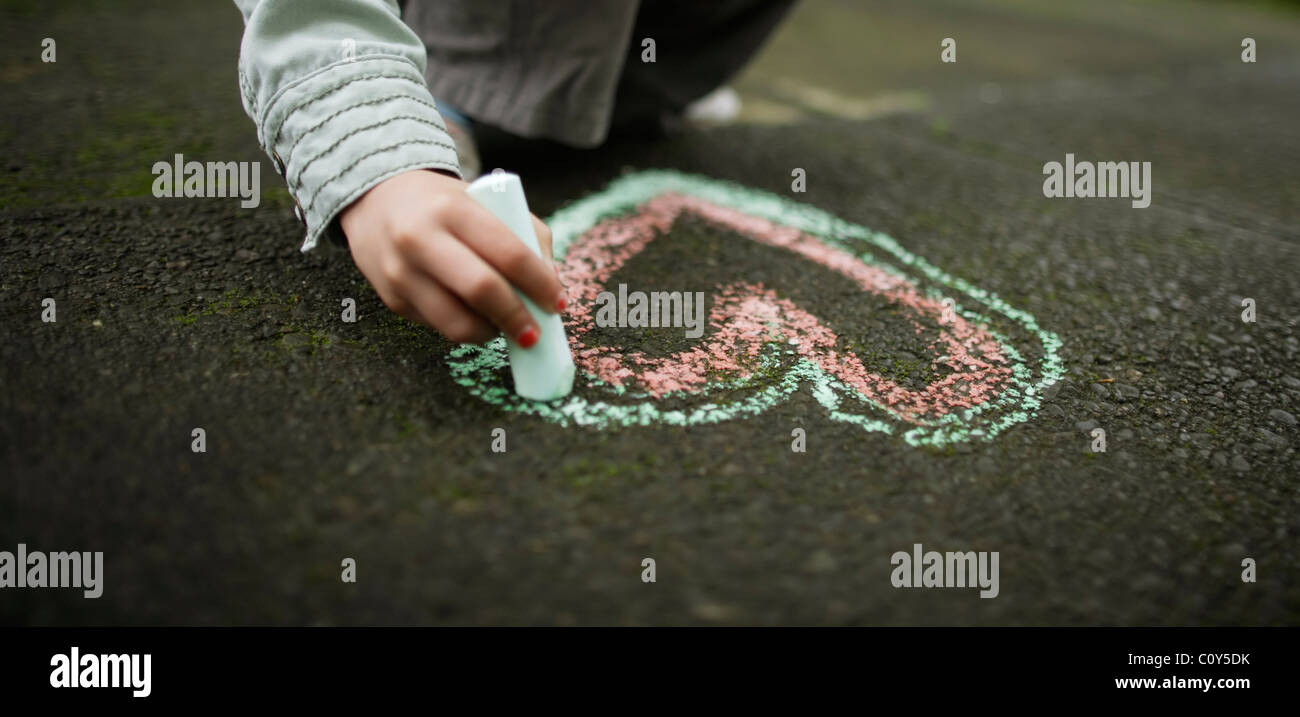 Girl drawing chalk heart on ground - Stock Image