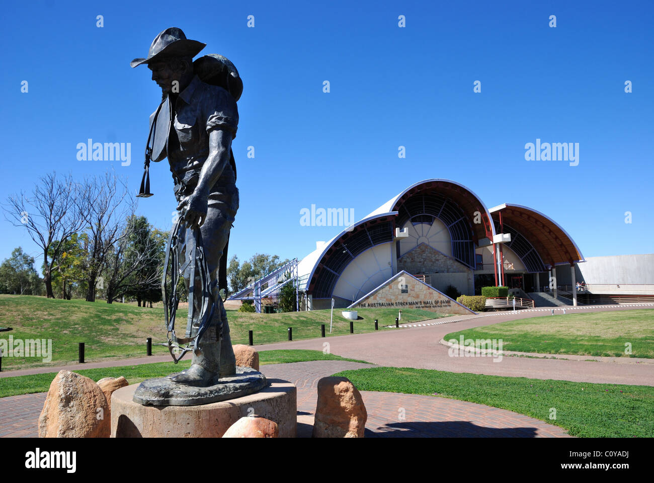 Stockman statue with Stockman's Hall of Fame building in background, Longreach, Queensland, Australia Stock Photo