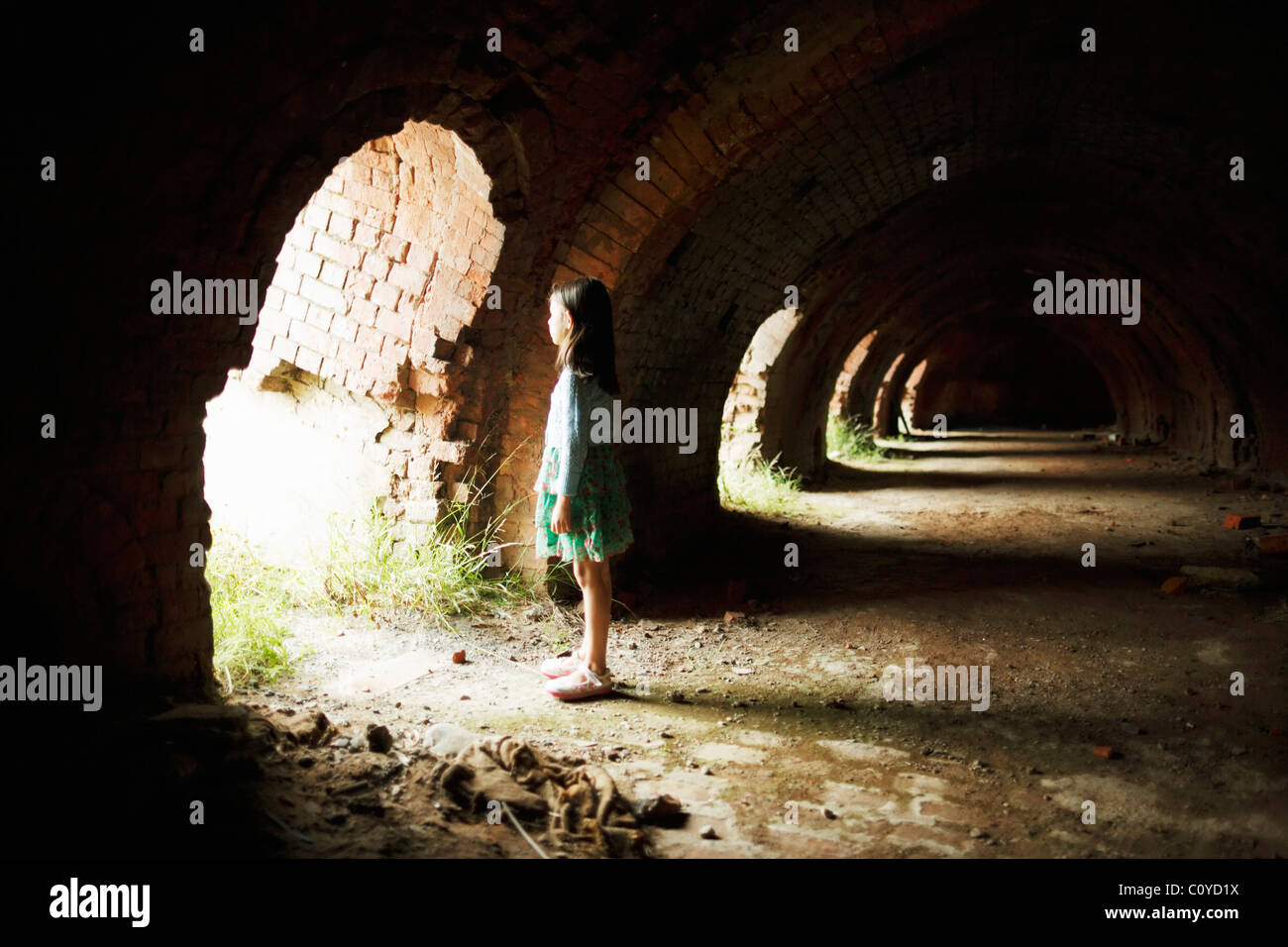 Girl stands in arches of derelict brick oven - Stock Image