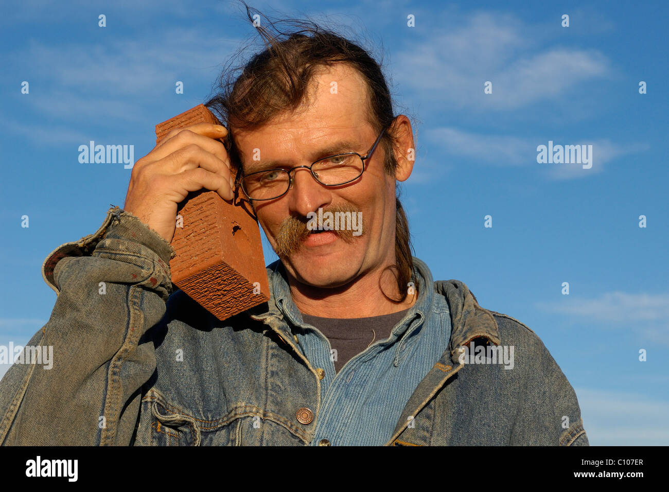 A scruffy man uses a brick as a mobil phone Stock Photo