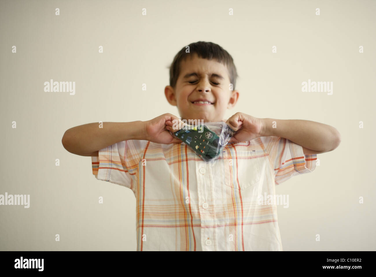 Boy tries hard to pull apart plastic bag containing toy - Stock Image