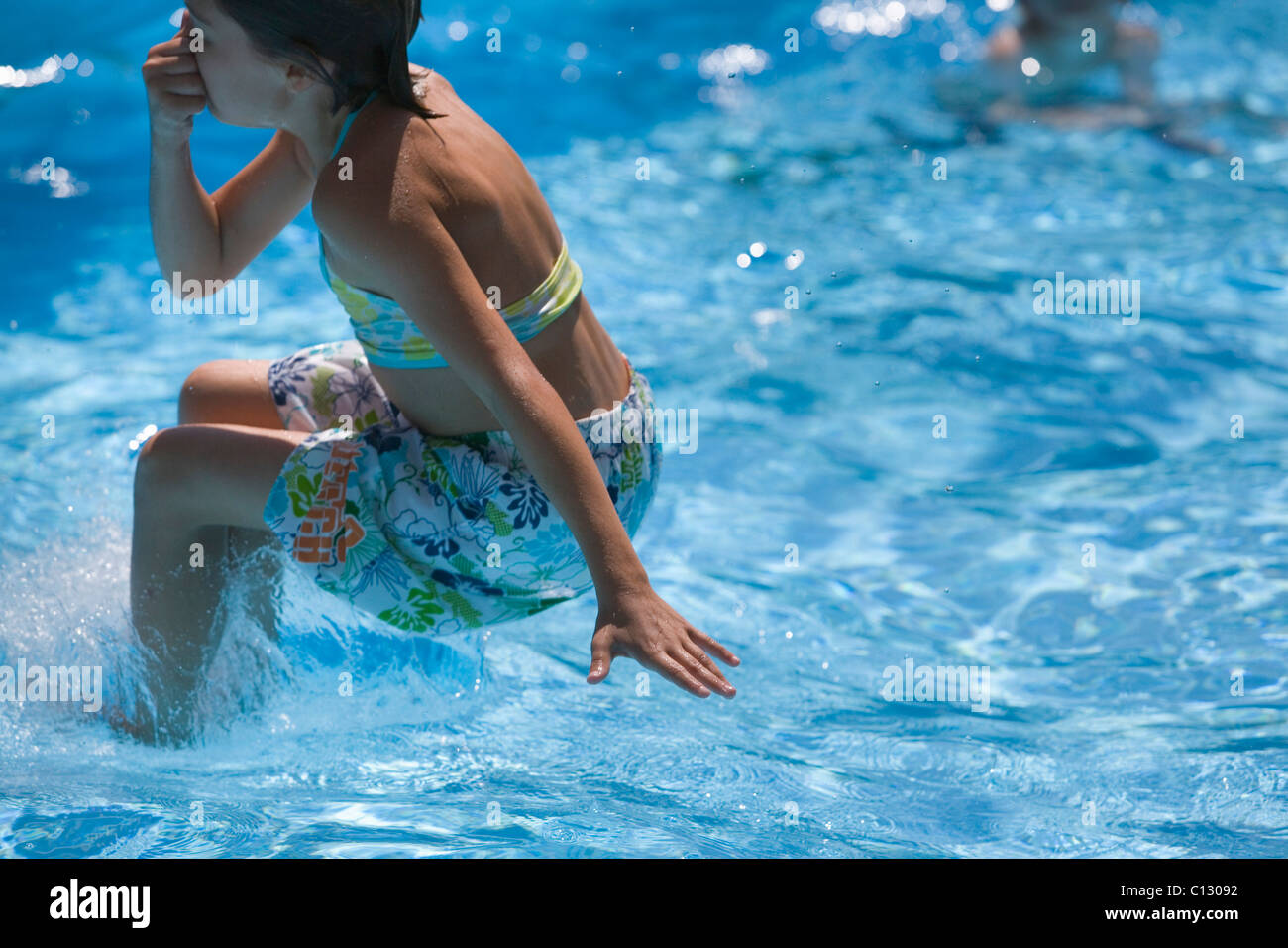 young girl jumping into swimming pool - Stock Image
