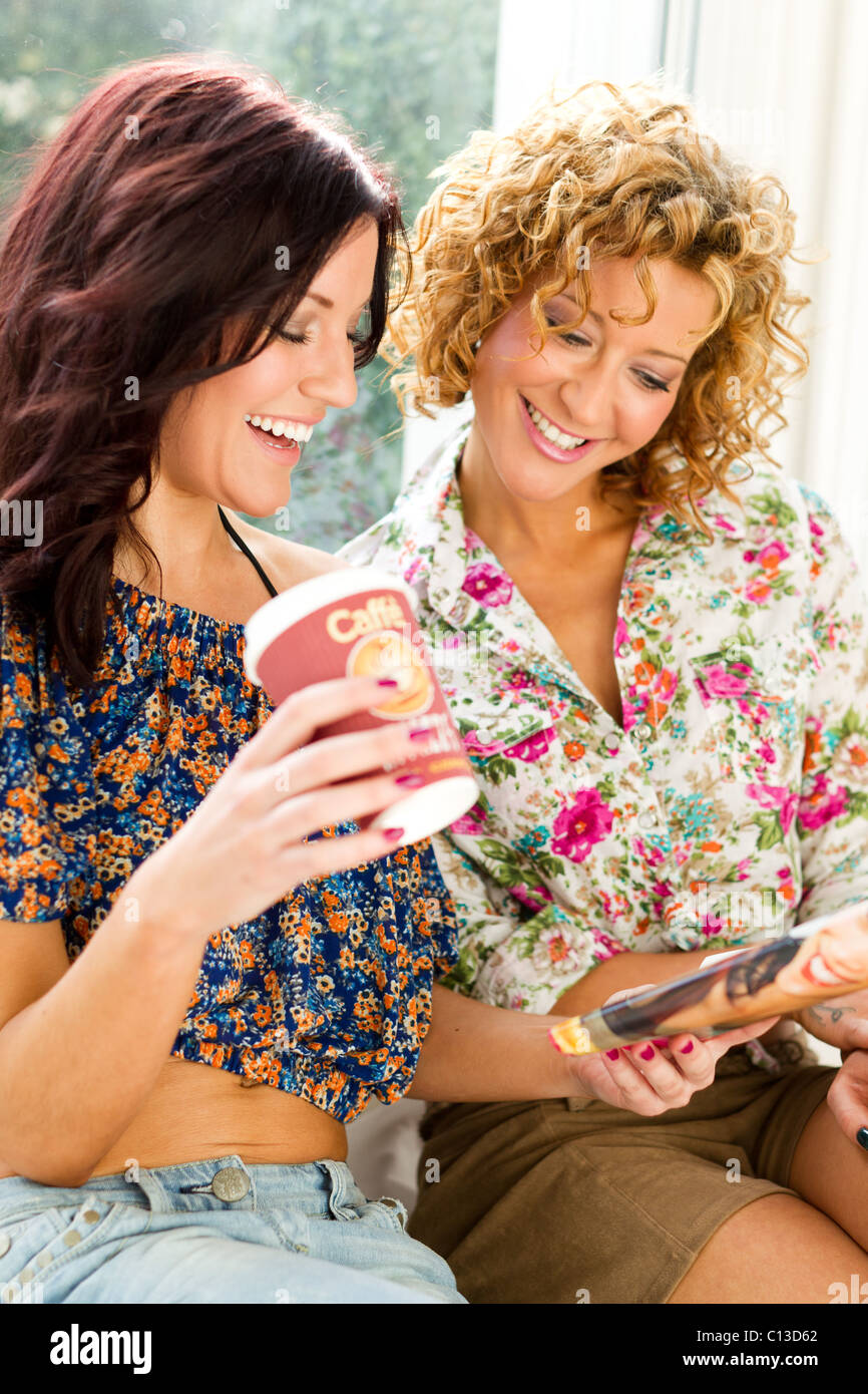 Two girls relaxing reading a magazine - Stock Image