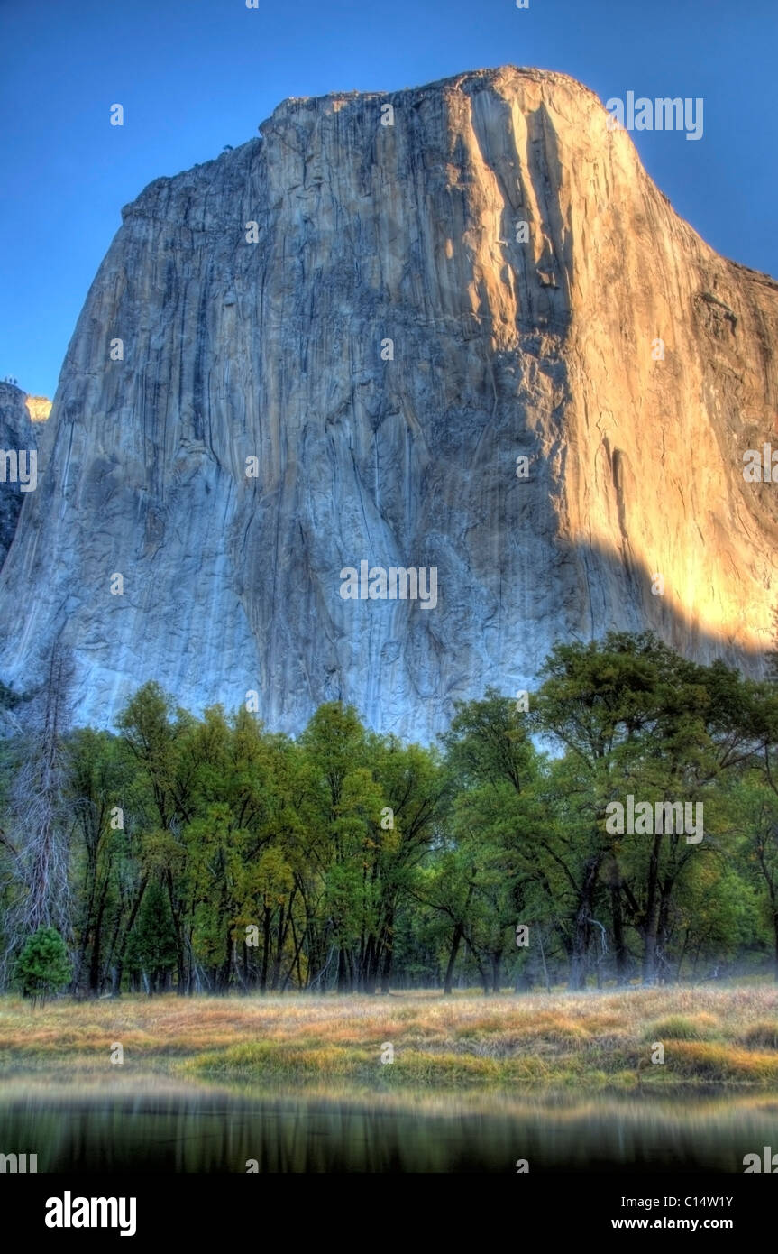 Looking over the Merced River, early morning sunlight hits El Capitan in Yosemite National Park, CA. - Stock Image