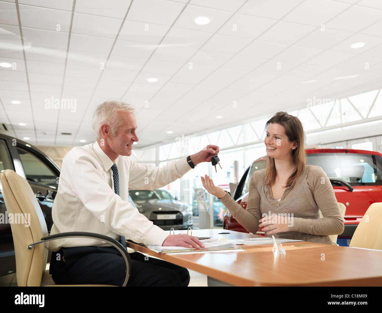 Salesman and customer in car dealership - Stock Image