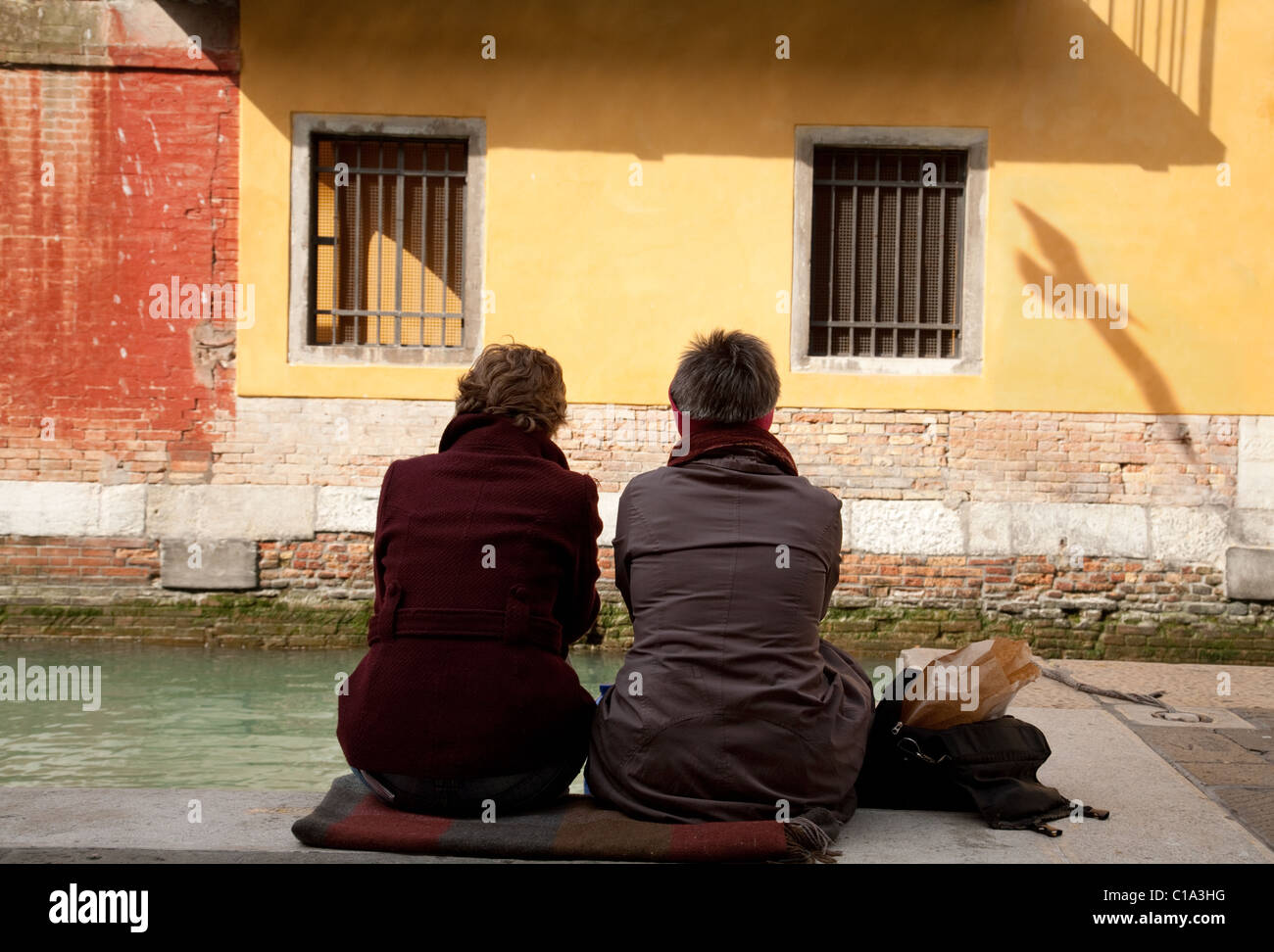 a-copule-sitting-by-the-canal-in-venice-italy-C1A3HG.jpg