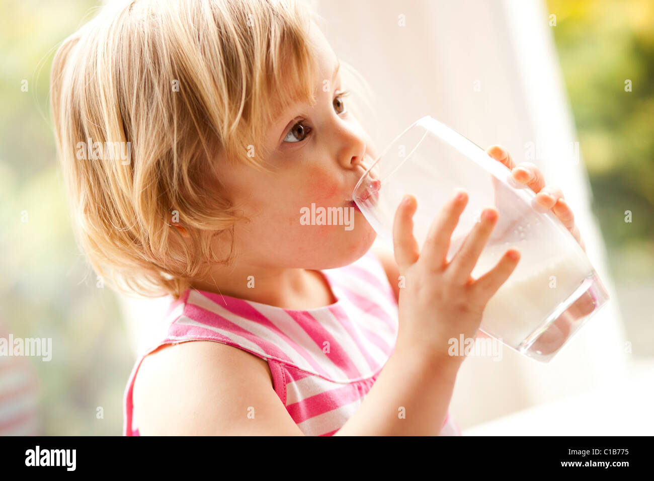 Child drinking glass of milk - Stock Image