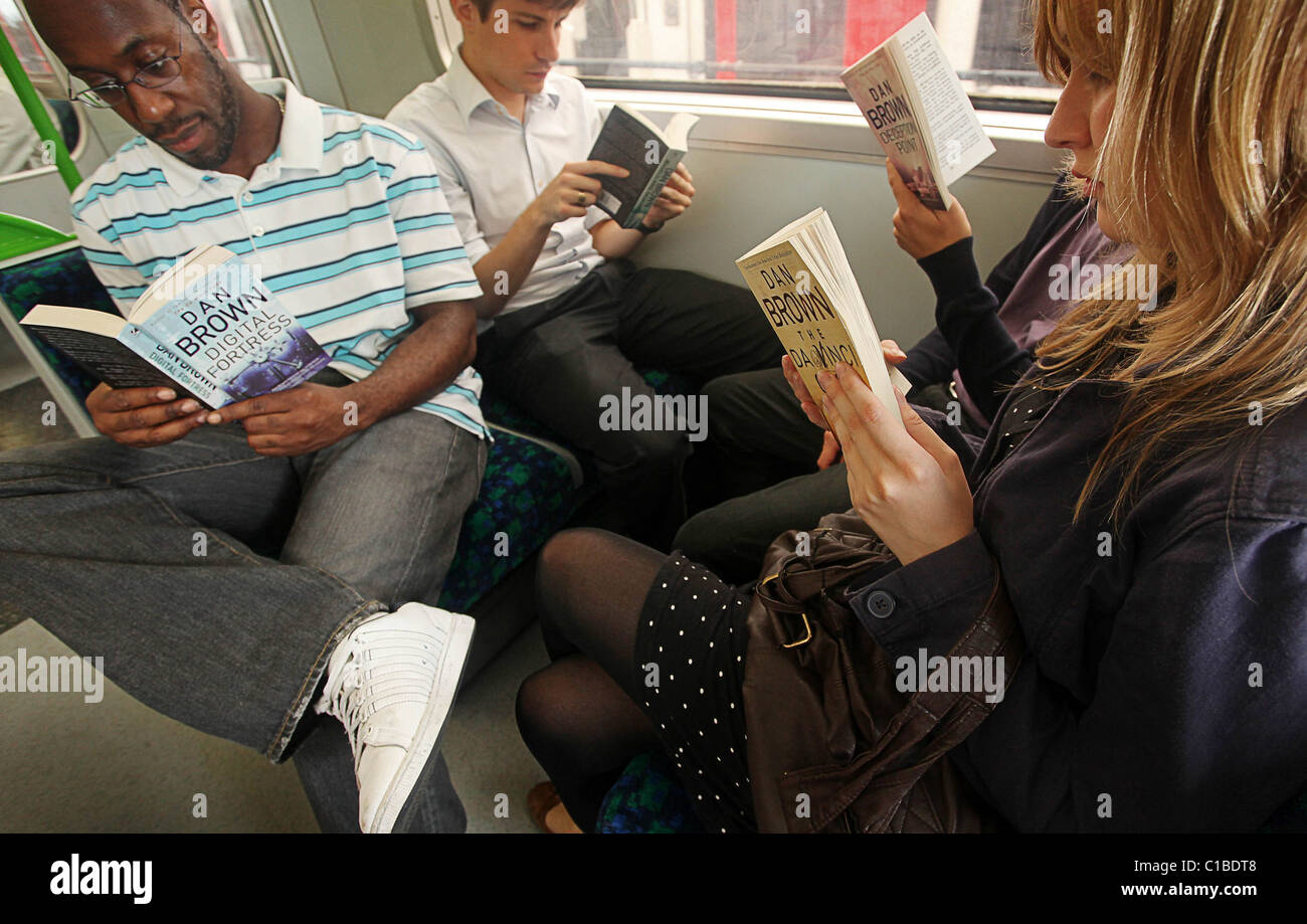 Commuters (posed) reading a selection of Dan Brown books on the London underground train -12th of August 2009. - Stock Image