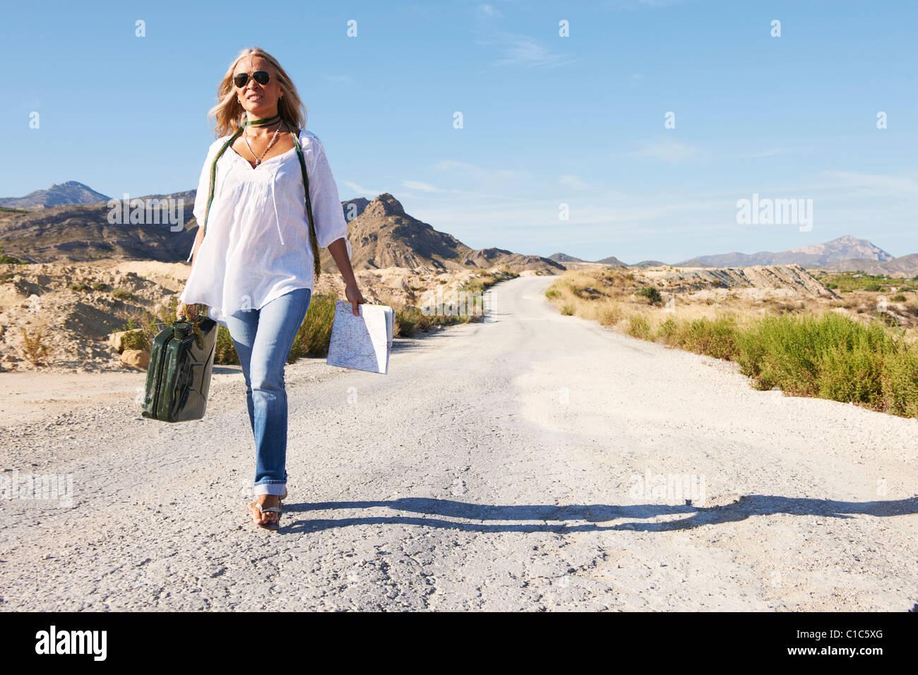Woman walking alone on dusty road - Stock Image