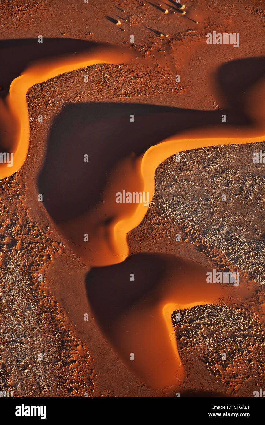 Sunrise enhances patterns made by sand dunes. Sossusvlei in the Namib desert. Namib-Naukluft N.P, Namibia. - Stock Image