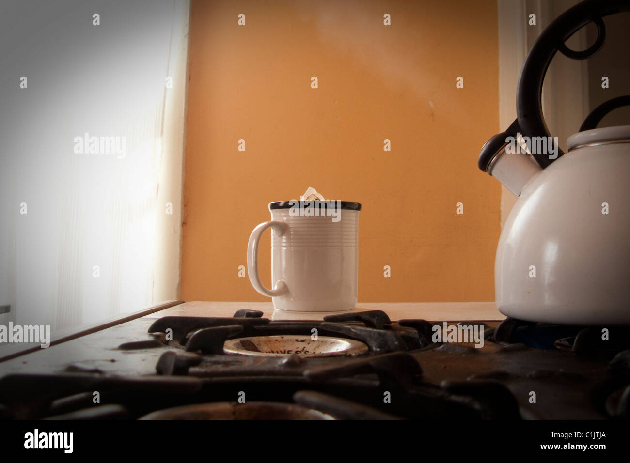 tea pot, cup, and steam on stove - Stock Image