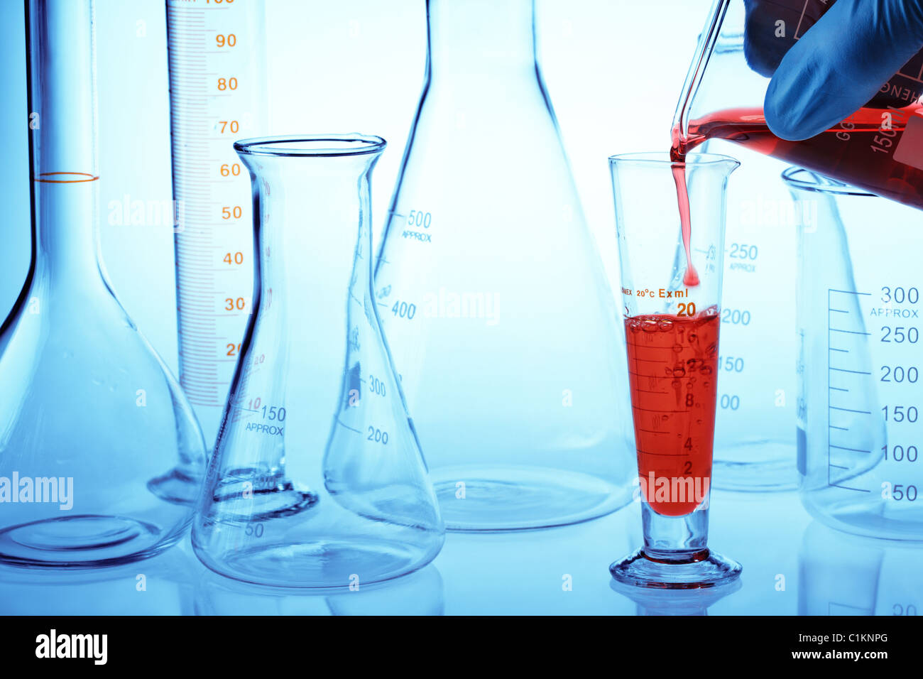 Scientist hand pouring liquid in a research lab. - Stock Image