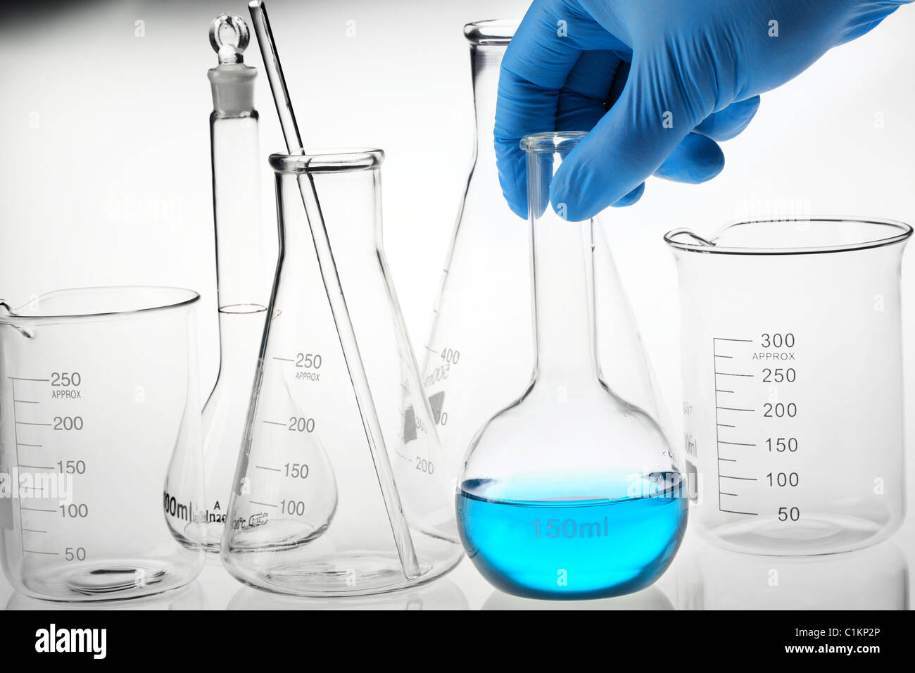 Scientist hand holding a flask in a research lab. - Stock Image