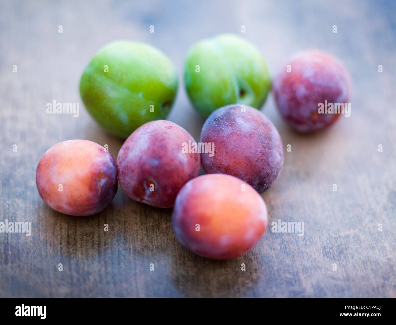 Green and purple plums on wooden table Stock Photo