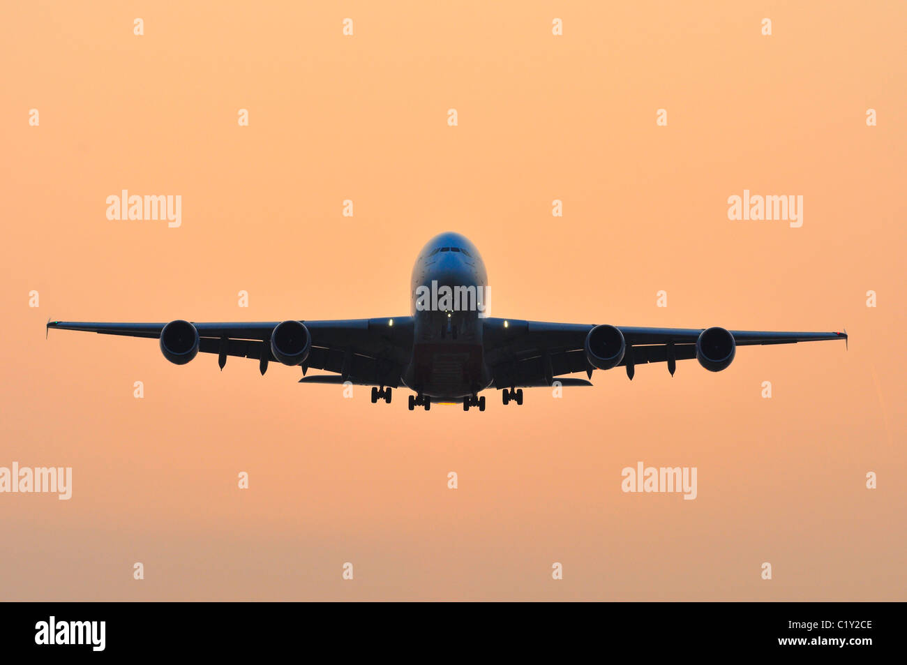 Airbus A380 Airplane coming into Land during sunset at Heathrow Airport - Stock Image