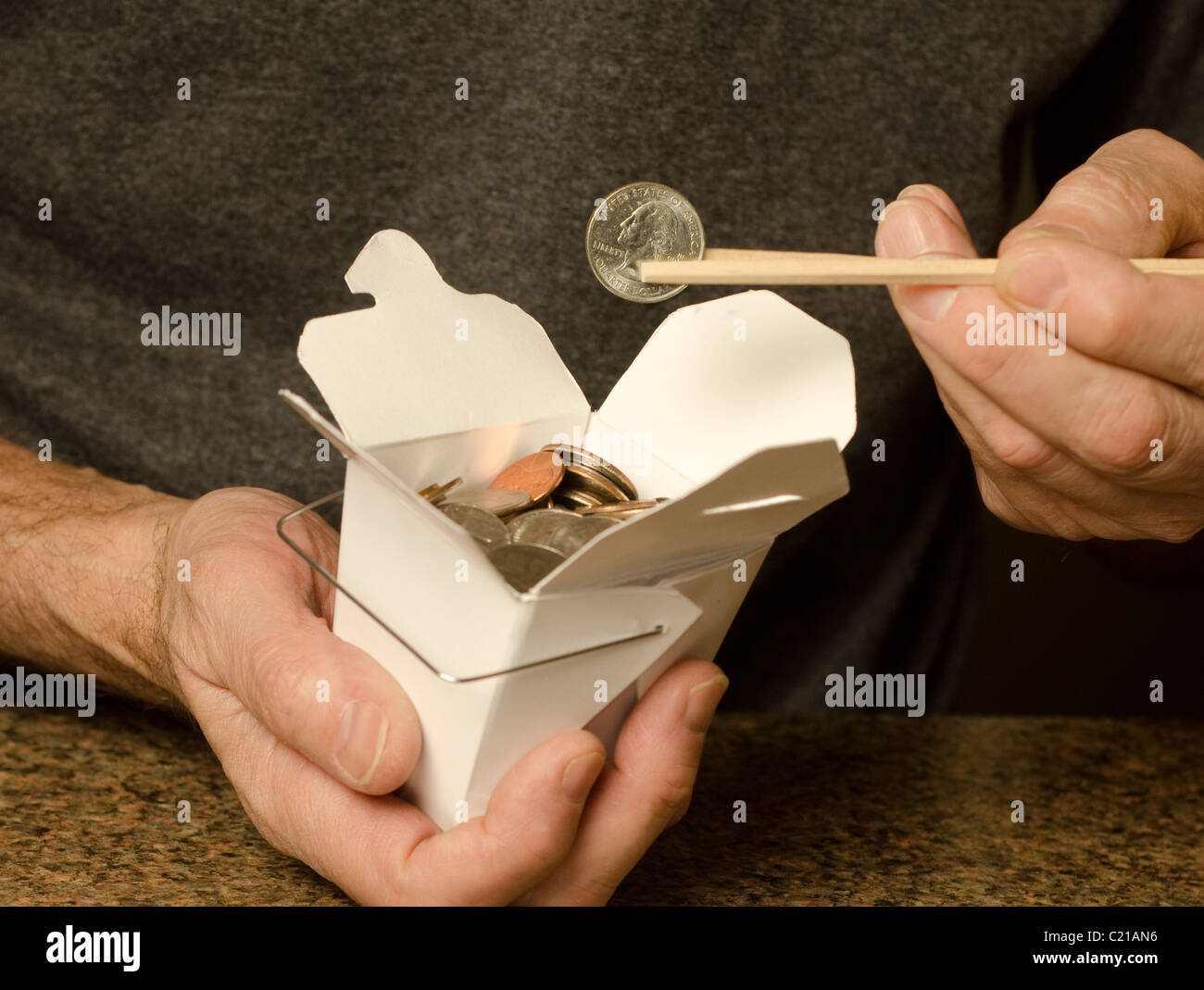 man holding Chinese food container containing US currency - Stock Image