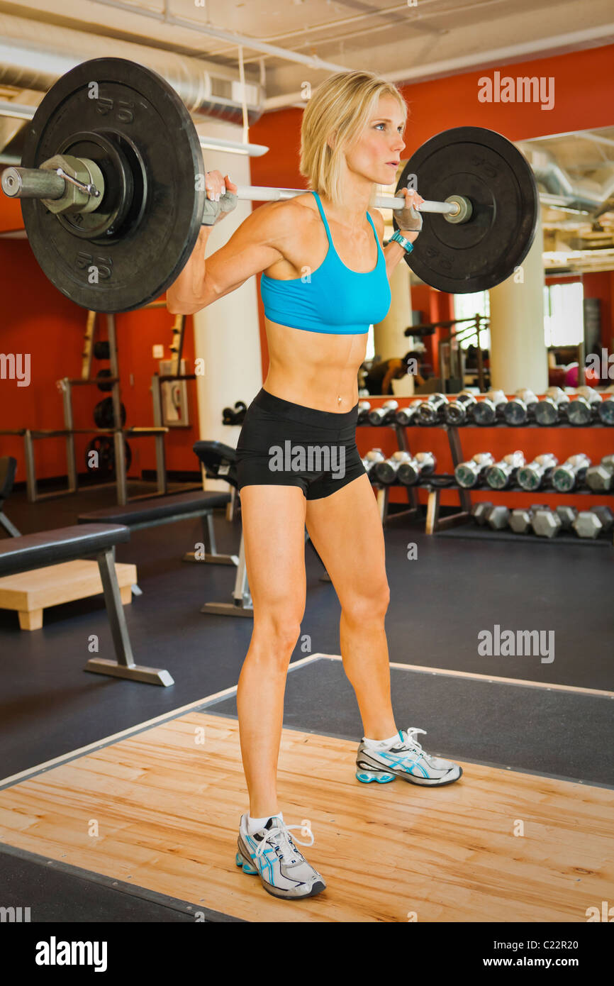 A physically fit woman doing squats in a health club weight room. - Stock Image