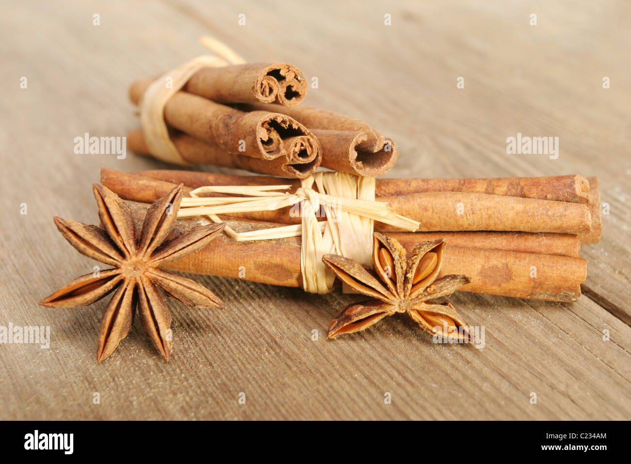 Cinnamon and star anise spices on old weathered and cracked wood with selective shallow focus - Stock Image