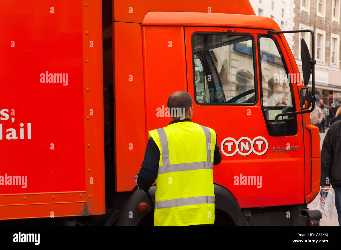 A TNT courier by his lorry in Norwich , Norfolk , England , Britain , Uk - Stock Image