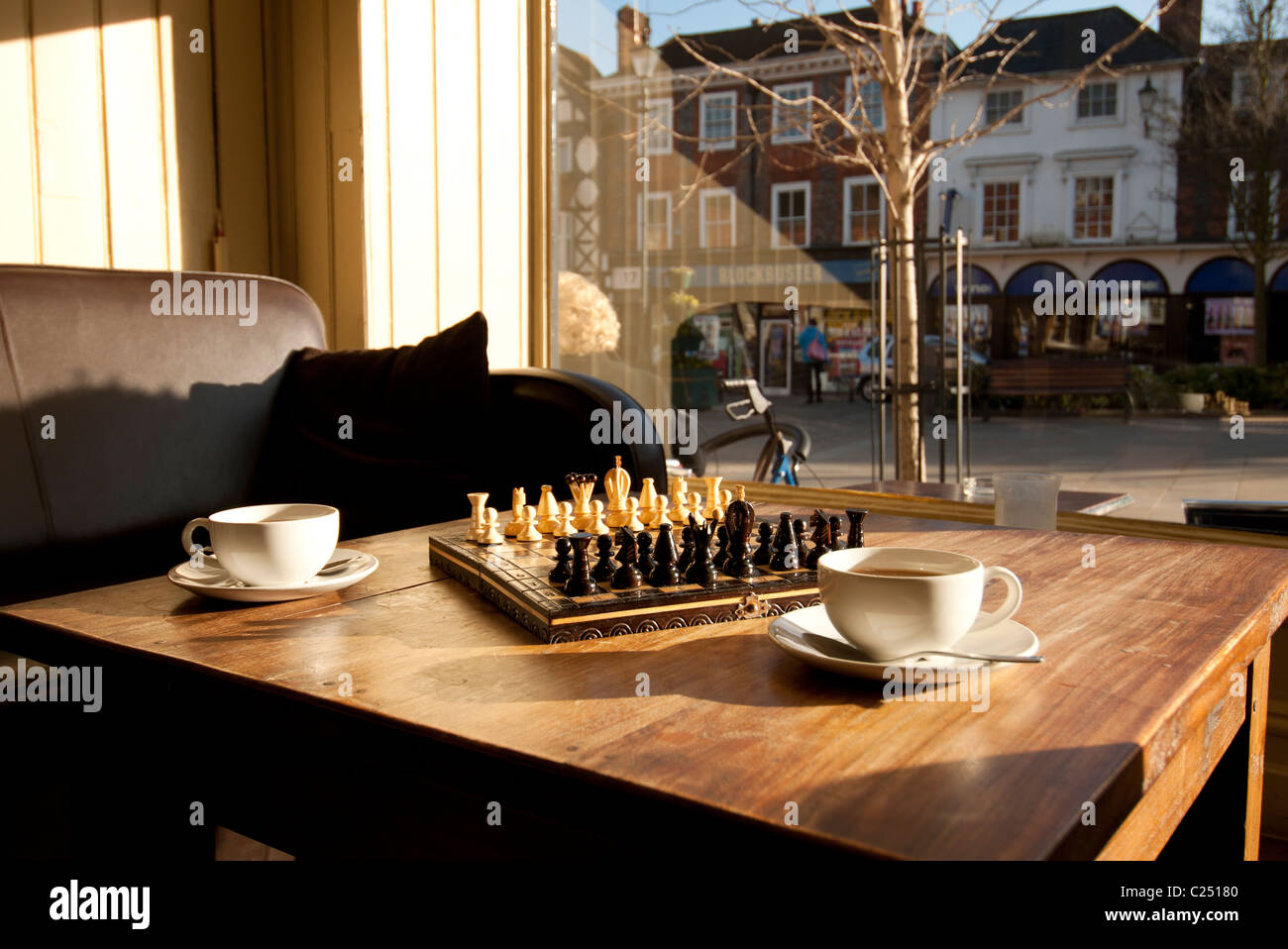 Game Of Chess Set Out On A Coffee Table With Two Cups