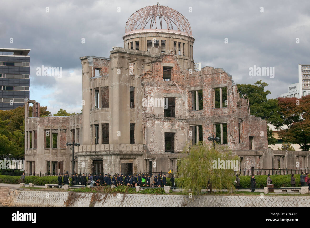 Genbaku Dome (Atomic Bomb Dome) with students in foreground, Hiroshima Peace Memorial Park, Hiroshima, Japan. - Stock Image