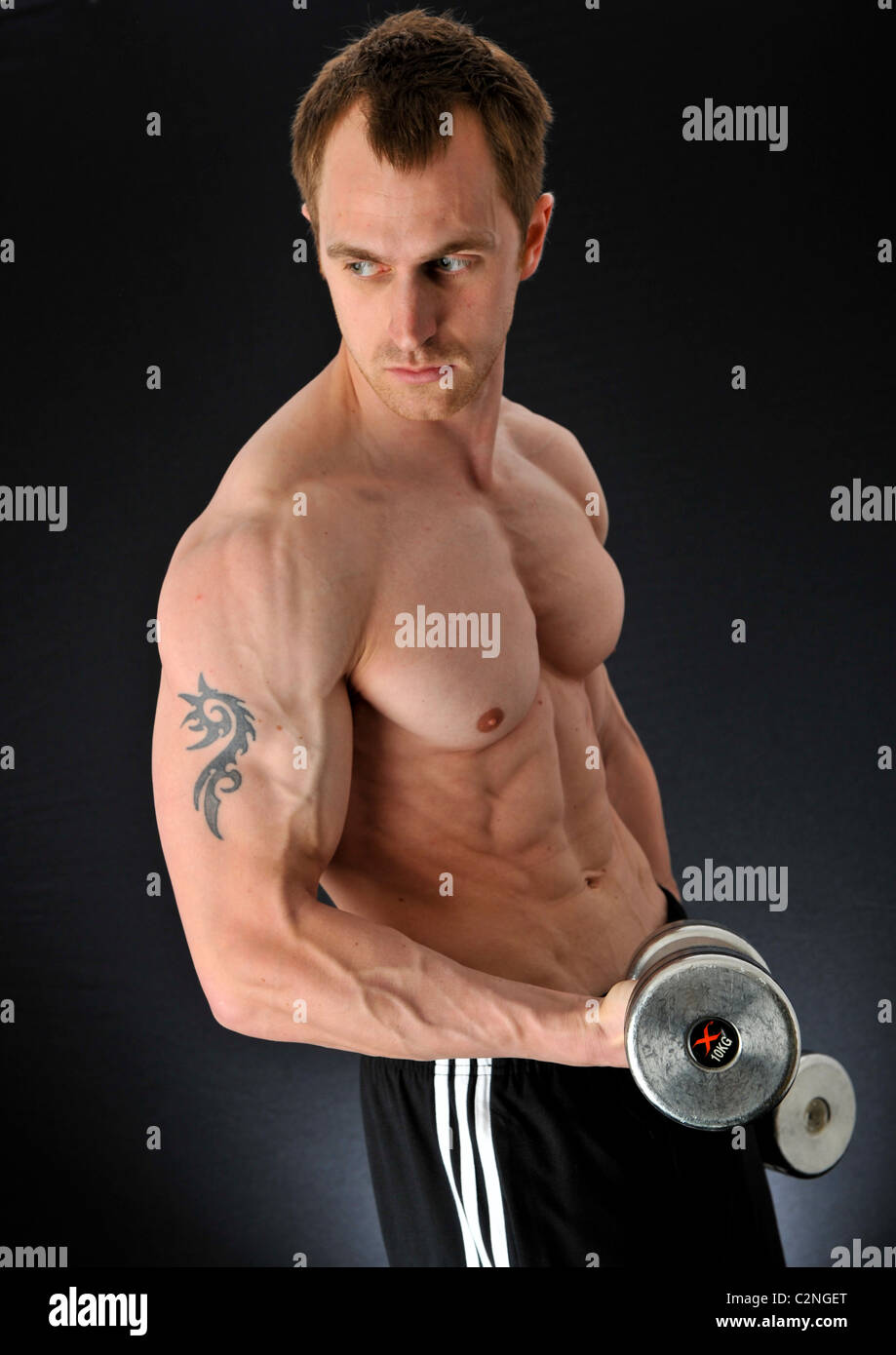Strong handsome bodybuilder lifting weights to enhance his training abilities to build healthy masculinity through - Stock Image