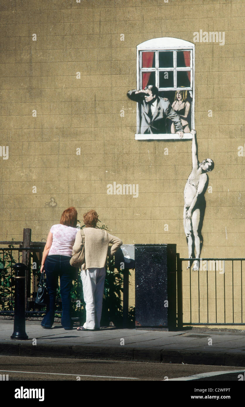 Wall painting by Banksy of naked man hanging from window ledge Park ...