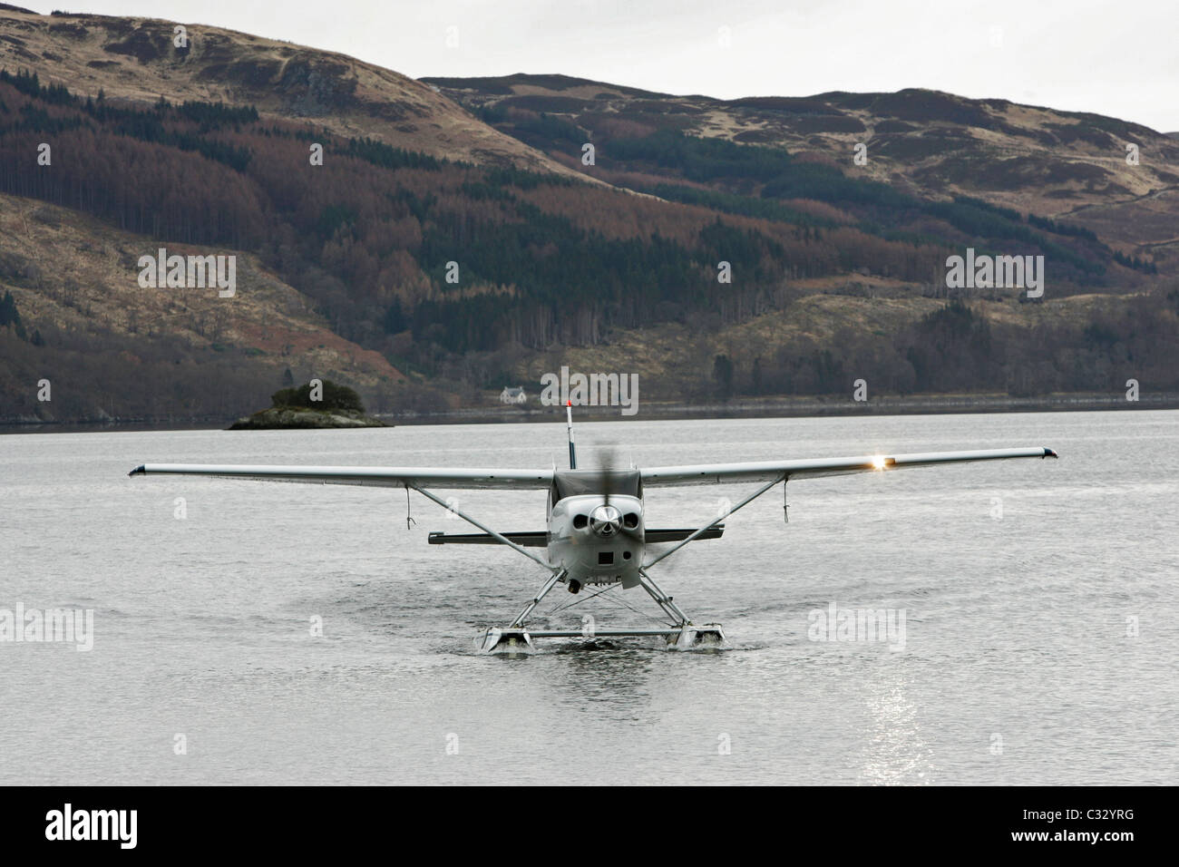 One of Loch Lomond Seaplanes aircraft taxiing towards shore on Loch Lomond - Stock Image